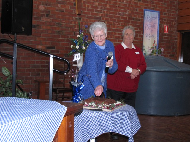 Member Nancy Coleman about to cut the cake, watched by current leader Corinne Hampel